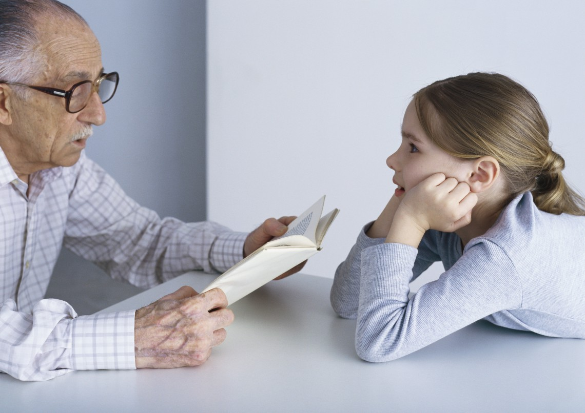 ©Laurence Mouton/6PA/MAXPPP ; Grandfather reading book to girl, sitting at table.
